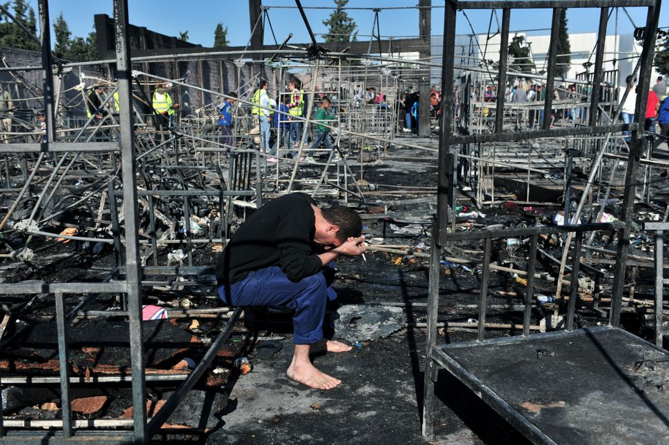 A man holds his head in his hands as he sits among bed frames burned by a fire thattore through a refugee camp in Diava