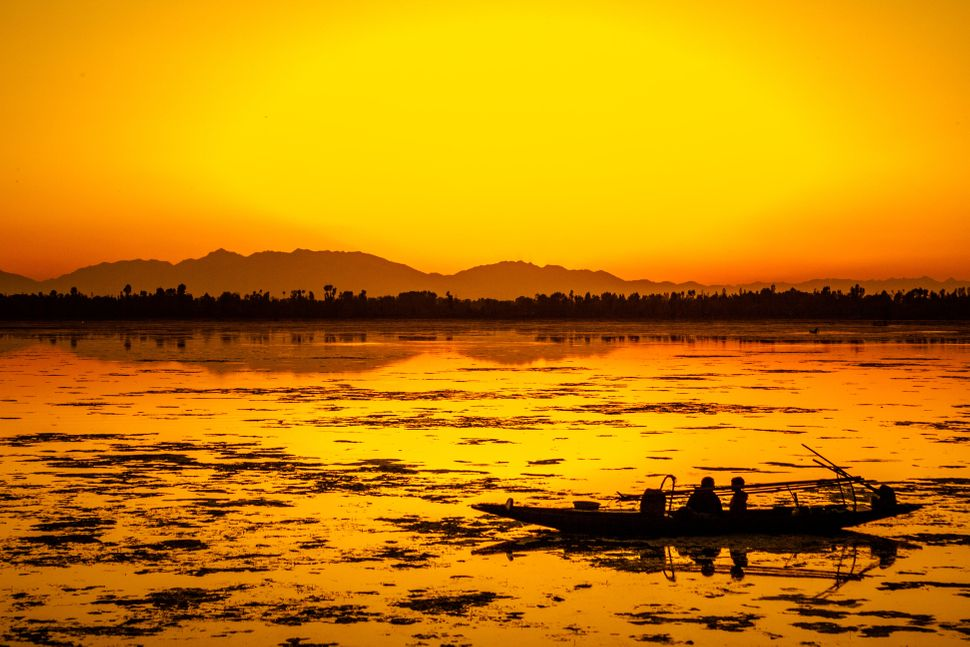 Fishermen resting in their Shikara boat are silhouetted against the setting sun at Dal lake in Srinagar, India, on May 3.