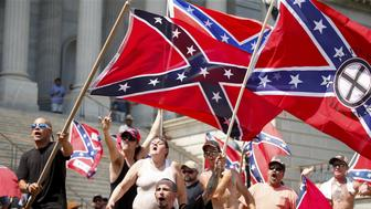 Members of the Ku Klux Klan yell as they fly Confederate flags during a rally at the statehouse in Columbia, South Carolina July 18, 2015. A Ku Klux Klan chapter and an African-American group planned overlapping demonstrations on Saturday outside the South Carolina State House, where state officials removed the Confederate battle flag last week. REUTERS/Chris Keane?      TPX IMAGES OF THE DAY