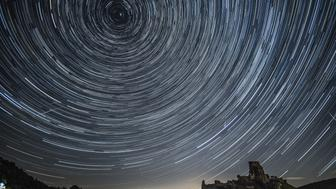 CORFE CASTLE, UNITED KINGDOM - AUGUST 12:  (EDITORS NOTE: THIS IS A COMPOSITE IMAGE) Satellites, planes and comets transit across the night sky under stars that appear to rotate above Corfe Castle on August 12, 2016 in Corfe Castle, United Kingdom. The Perseids meteor shower occurs every year when the Earth passes through the cloud of debris left by Comet Swift-Tuttle, and appear to radiate from the constellation Perseus in the north eastern sky.  (Photo by Dan Kitwood/Getty Images)