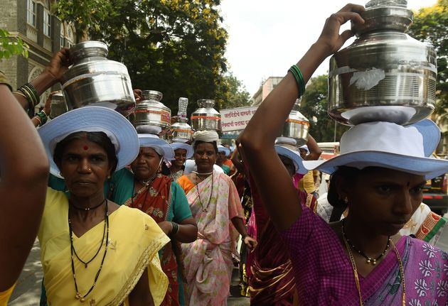 Indian villagers from drought affected areas carry pots as they take part in a rally to spread awareness...