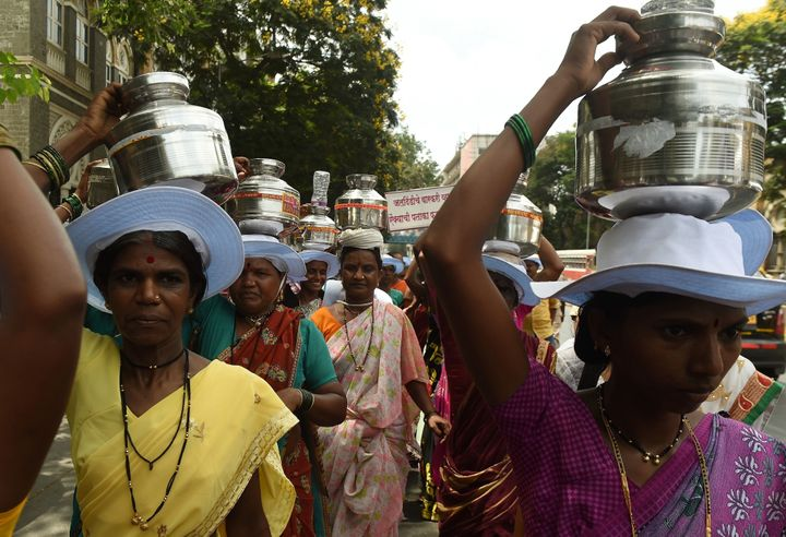 Indian villagers from drought affected areas carry pots as they take part in a rally to spread awareness on water usage in Mu