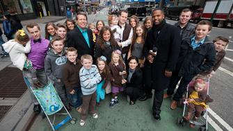 NEW YORK, NY - MARCH 11:  AJ Calloway and Hilaria Baldwin pose with the Duggar family during their visit with 'Extra' in Times Square on March 11, 2013 in New York City.  (Photo by D Dipasupil/Getty Images for Extra)