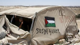A Palestinian man looks out of a tent in Susiya village, south of the West Bank city of Hebron July 20, 2015. Sitting under a fig tree to escape the searing sun, Jihad Nuwaja looks out on the only land he knows - the dry expanse of the Hebron hills in the southern West Bank. Within days, his home is set to be demolished and he, his wife and 10 children expelled. Nuwaja's family is one of handful living in tents and prefabricated structures at Susiya, a Palestinian village spread across several rocky hillsides between a Jewish settlement to the south and a Jewish archaeological site to the north - land Israel has occupied since the 1967 Middle East war. REUTERS/Mussa Qawasma