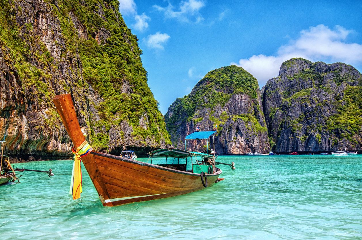 Long tail wooden boat at Maya Bay on Ko Phi Phi Le, made famous by the movie titled 'The Beach'. Beautiful cloudscape over the turquoise water and green rocks in Maya Bay, Phi Phi Islands, Thailand.