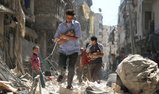 Syrian men carrying babies make their way through the rubble of destroyed