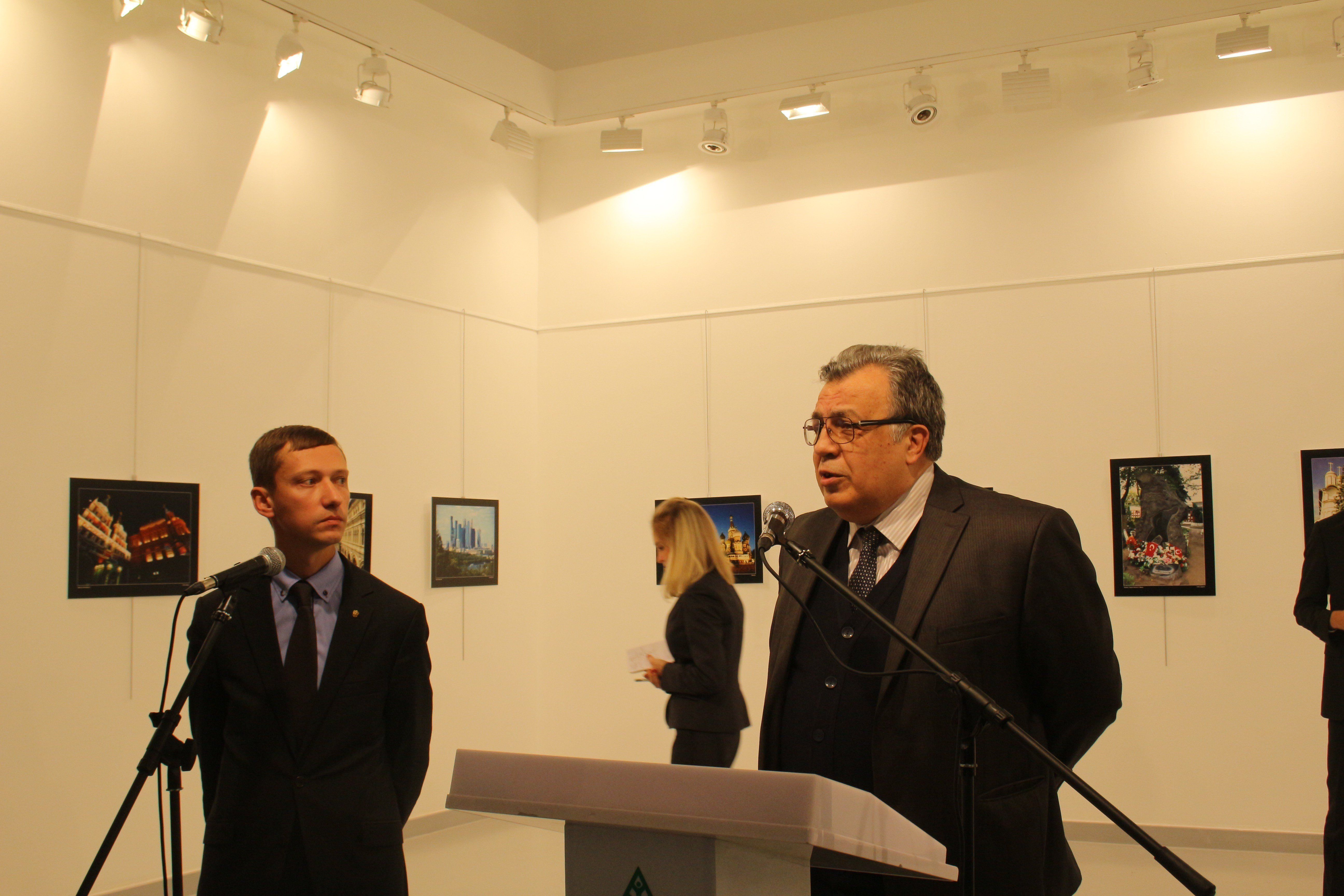 Russian Ambassador to Turkey, Andrei Karlov (R) gives a speech as he visits an art fair at Modern Art...
