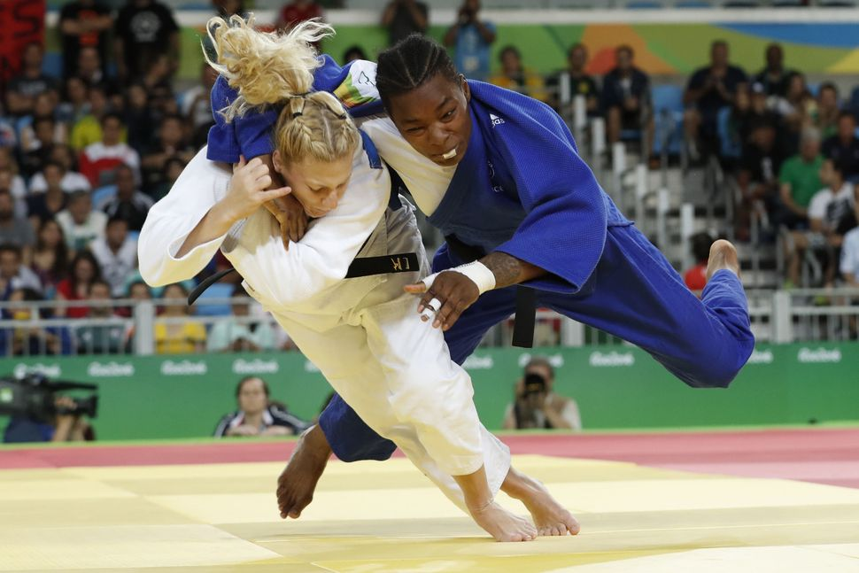 France's Audrey Tcheumeo (blue) competes with US Kayla Harrison (white) during their women's -78kg judo contest gold medal ma