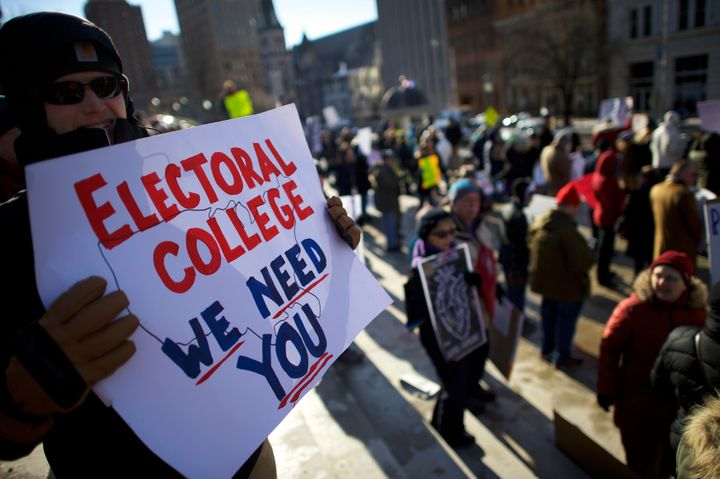 Protesters rally against President-elect Donald Trump Monday outside the Pennsylvania State Capitol Building in Harrisburg before Electoral College members cast their votes for president.