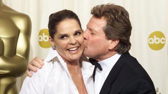 """Ryan O'Neal (R) kisses Ali McGraw backstage during the 74th annual Academy Awards in Hollywood, March 24, 2002. The two, who starred in the movie """"Love Story"""" presented the Jean Hersholt Humanitarian Award to Arthur Hiller, who directed them in the movie. REUTERS/Andy Clark PICTURE EMBARGOED FROM REDISTRIBUTION FOR ONLINE/INTERNET USE UNTIL CONCLUSION OF ACADEMY AWARDS TELECAST  FG/ME"""