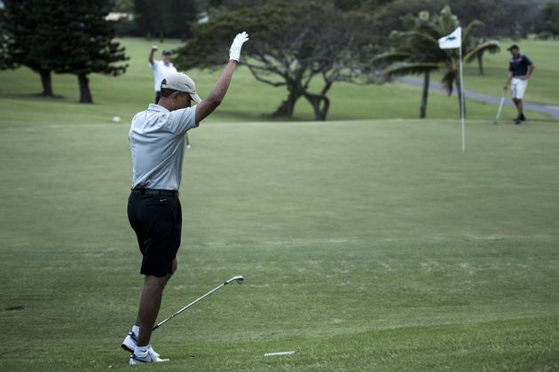 US President Barack Obama reacts on the 18th hole of the Mid-Pacific Country Club's golf course December...