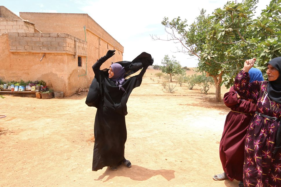 A woman removes a niqab she was wearing after Syria Democratic Forces took control of her villageon the outskirts of Ma