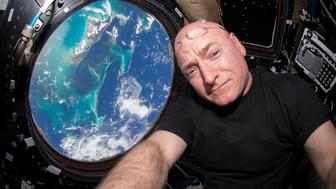NASA astronaut Scott Kelly is seen inside the cupola of the International Space Station, a special module that provides a 360-degree viewing of the Earth and the station in this undated photo released on March 11, 2016. The astronaut who currently holds the American record for most time spent in space, Scott Kelly, will retire from NASA as of April 1, NASA said on Friday.  REUTERS/NASA/Handout via Reuters