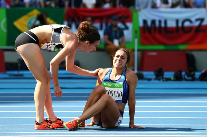 Abbey D'Agostino of the United States (R) is assisted by Nikki Hamblin of New Zealand after a collision during the Women's 50