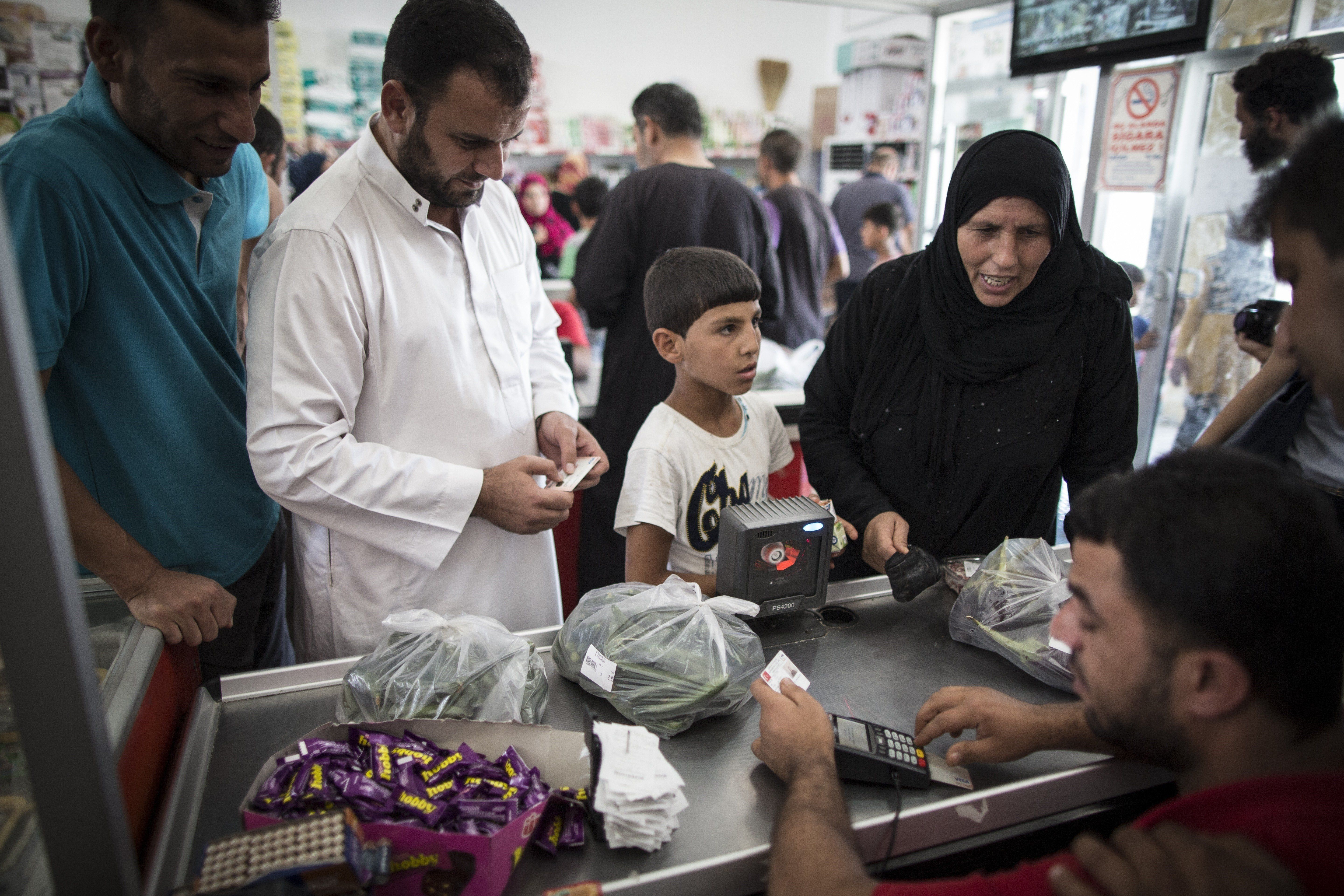 SANLIURFA, TURKEY - SEPTEMBER 24: Refugees shop at a market with their bank card given by the Turkish Red Crescent at a tent city in the Akcakale District of Sanliurfa, Turkey on September 24, 2015. Turkish Red Crescent provided bank cards for the refugees and gives 85 Turkish Liras every month per person. 260 thousand Syrians who have escaped war and found asylum in Turkey are now living in camps with opportunities that mean they don't miss what they've left behind. (Photo by Aykut Unlupinar/Anadolu Agency/Getty Images)