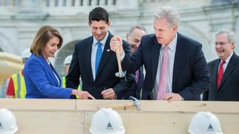 UNITED STATES - SEPTEMBER 21: House Majority Leader Kevin McCarthy, R-Calif., pulls the bent nail of Sen. Charles Schumer, D-N.Y., center, as Speaker Paul Ryan, R-Wis., second from left, Senate Majority Leader Mitch McConnell, R-Ky., and House Minority Leader Nancy Pelosi, D-Calif., look on, during a First Nail Ceremony that launches the construction of the Inaugural platform on the West Front of the Capitol, September 21, 2016. Sen. Roy Blunt, R-Mo., chairman of the Joint Congressional Committee on Inaugural Ceremonies, and Architect of the Capitol Stephen Ayers also participated. The next President will take the oath of office, January 20, 2017. (Photo By Tom Williams/CQ Roll Call)