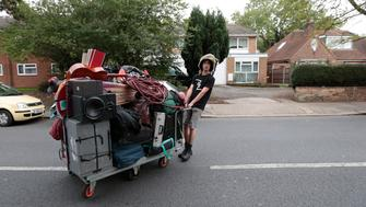 A squatter moves his belongings after being evicted from a housing estate in north London, Britain September 24, 2015. Local media reports that the estate has been earmarked for demolition and a development of luxury homes is planned for the site. REUTERS/Suzanne Plunkett