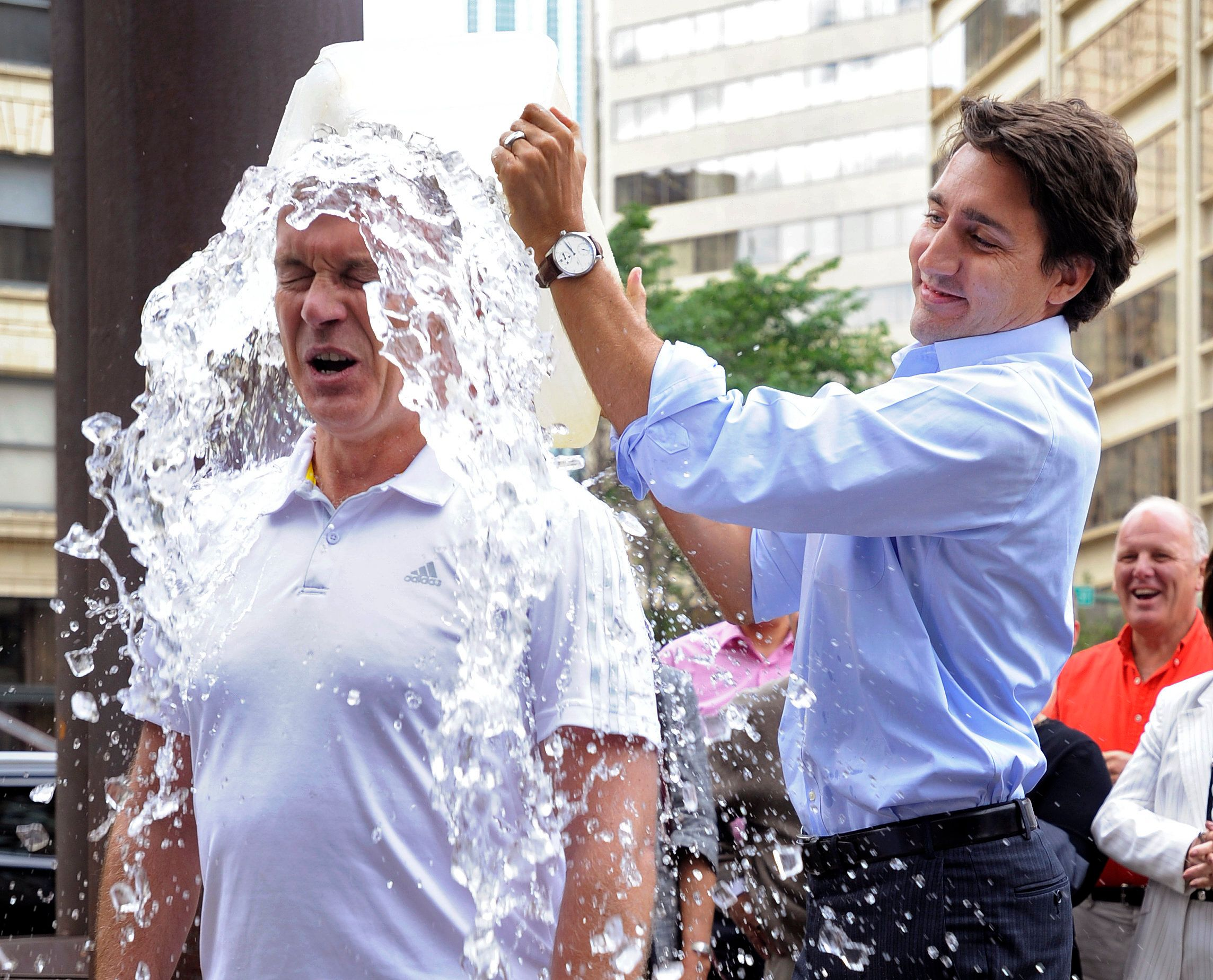 Liberal leader Justin Trudeau (R) dumps a bucket of ice water onto Liberal MP Sean Casey for the ALS ice bucket challenge during a break in the Federal Liberal summer caucus meetings in Edmonton August 19, 2014.  REUTERS/Dan Riedlhuber/File Photo