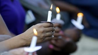 Mourners hold candles at a vigil for Baton Rouge police officer Montrell Jackson, who was shot and killed Sunday morning, in Baton Rouge, Louisiana, U.S. July 19, 2016.  REUTERS/Jonathan Bachman