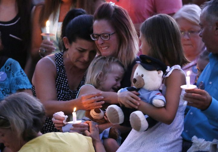 Dechia Gerald, wife of slain officer Matthew Gerald, holds her two daughters at a vigil in Baton Rouge, Louisiana, U.S. July