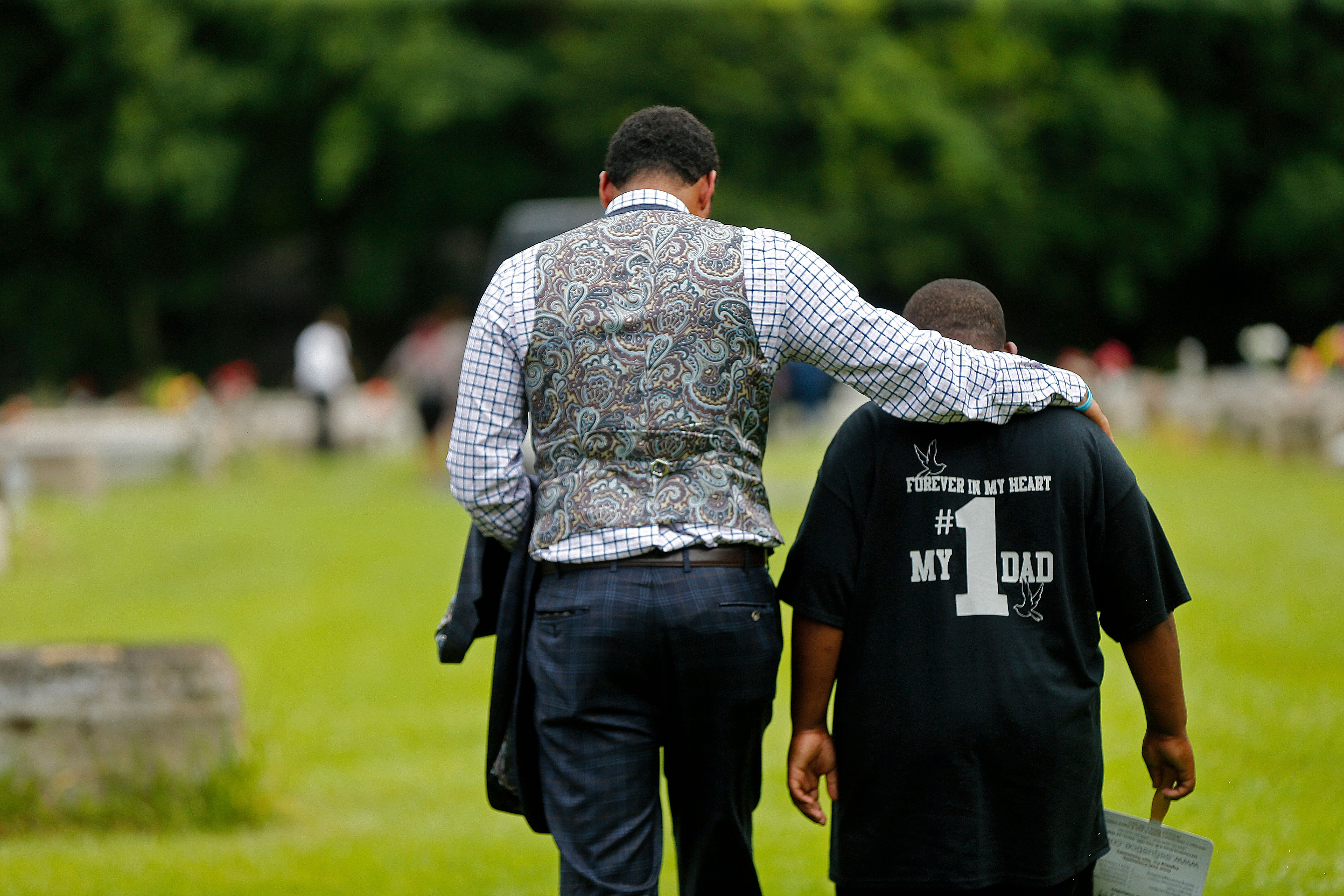 Family attorney Justin Bamberg (L), comforts Na'Quincy, 10, son of Alton Sterling, at the conclusion Alton's burial at the Mount Pilgrim Benevolent Society Cemetery in Baton Rouge, Louisiana, U.S., July 15, 2016.   REUTERS/Gerald Herbert/Pool