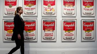 """Sotheby's worker, Isabelle Brown, poses with """"Campbell's Soup II"""" by Andy Warhol at Sotheby's in London March 15, 2013. The set of ten screen prints is expected to sell for 150,000 GB pounds (US$ 226,300) when it comes to auction on March 19. REUTERS/Luke MacGregor  (BRITAIN - Tags: ENTERTAINMENT SOCIETY BUSINESS)"""