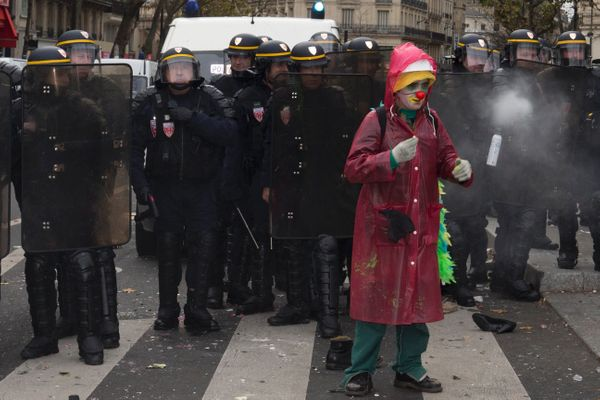 A protestor disguised as a clown stands in front of riot police during clashes following a rally against global warming on No