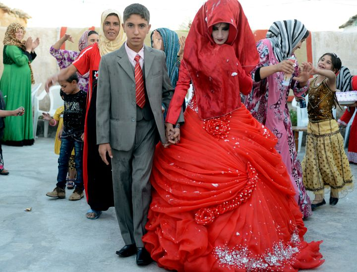 Hussein Younis Ali, 14 walks with his bride Nada Ali Hussein, 17, during the wedding party at his home in Tikrit, 150 km (93