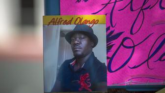EL CAJON, CA - SEPTEMBER 29: A photo of Alfred Olango, 38, hangs at a makeshift memorial at the site where he was shot by police earlier this week on September 29, 2016 in El Cajon, California. A family member called police to help Olango as he was acting erratically and walking through traffic, but shot him when he quickly pulled out an electronic cigarette device. He died later that evening.   (Photo by David McNew/Getty Images)