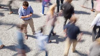 Man checking cell phone among rushing crowd