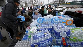 Volunteers distribute bottled water to help combat the effects of the crisis when the city's drinking water became contaminated with dangerously high levels of lead in Flint, Michigan, March 5, 2016.     REUTERS/Jim Young