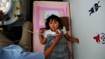 A doctor conducts a thyroid examination on four-year-old Maria Sakamoto, brought by her mother to the office of Iwaki Radiation Citizen Centre NPO, in Iwaki town, south of the tsunami-crippled Fukushima Daiichi nuclear power plant in Fukushima prefecture September 18, 2013. The non-profit organization offers free thyroid examination for children from Fukushima area. As the World Health Organisation (WHO) says children in Fukushima may have a higher risk of developing thyroid cancer after the Daiichi nuclear disaster two years ago, mothers in Fukushima worry that local health authorities are not doing enough. Picture taken September 18, 2013.   REUTERS/Damir Sagolj (JAPAN - Tags: DISASTER SOCIETY ENVIRONMENT)  ATTENTION EDITORS: PICTURE 52 OF 53 FOR PACKAGE 'BROKEN LIVES OF FUKUSHIMA'. TO FIND ALL IMAGES SEARCH 'FUKUSHIMA DAMIR'