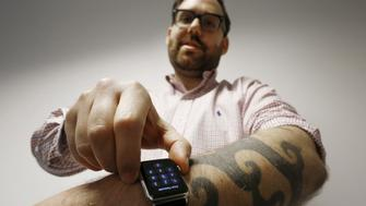 Reuters journalist Matt Siegel inputs his passcode onto his Apple Watch as his tattoos prevent the device's sensors from correctly detecting his skin, in Sydney, Australia, April 30, 2015. Early adopters of the Apple Watch, Apple Inc's first new product in five years, are complaining that a number of its key functions are disrupted by their tattoos. Owners of Apple Watch - including Siegel, who bought a 42mm version with stainless steel case and black classic buckle for A$1,029 (534 pounds) - have found that their inked skin confuses the sensors on the underside of the device.    REUTERS/Jason Reed