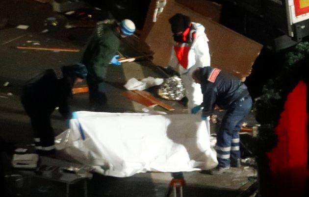 Police investigators cover a