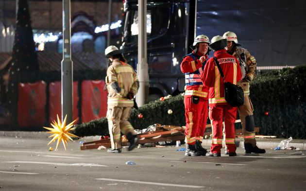 Paramedics and fire fighters talk beside a truck at a Christmas market in Berlin,