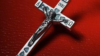 A crucifix against a red background.