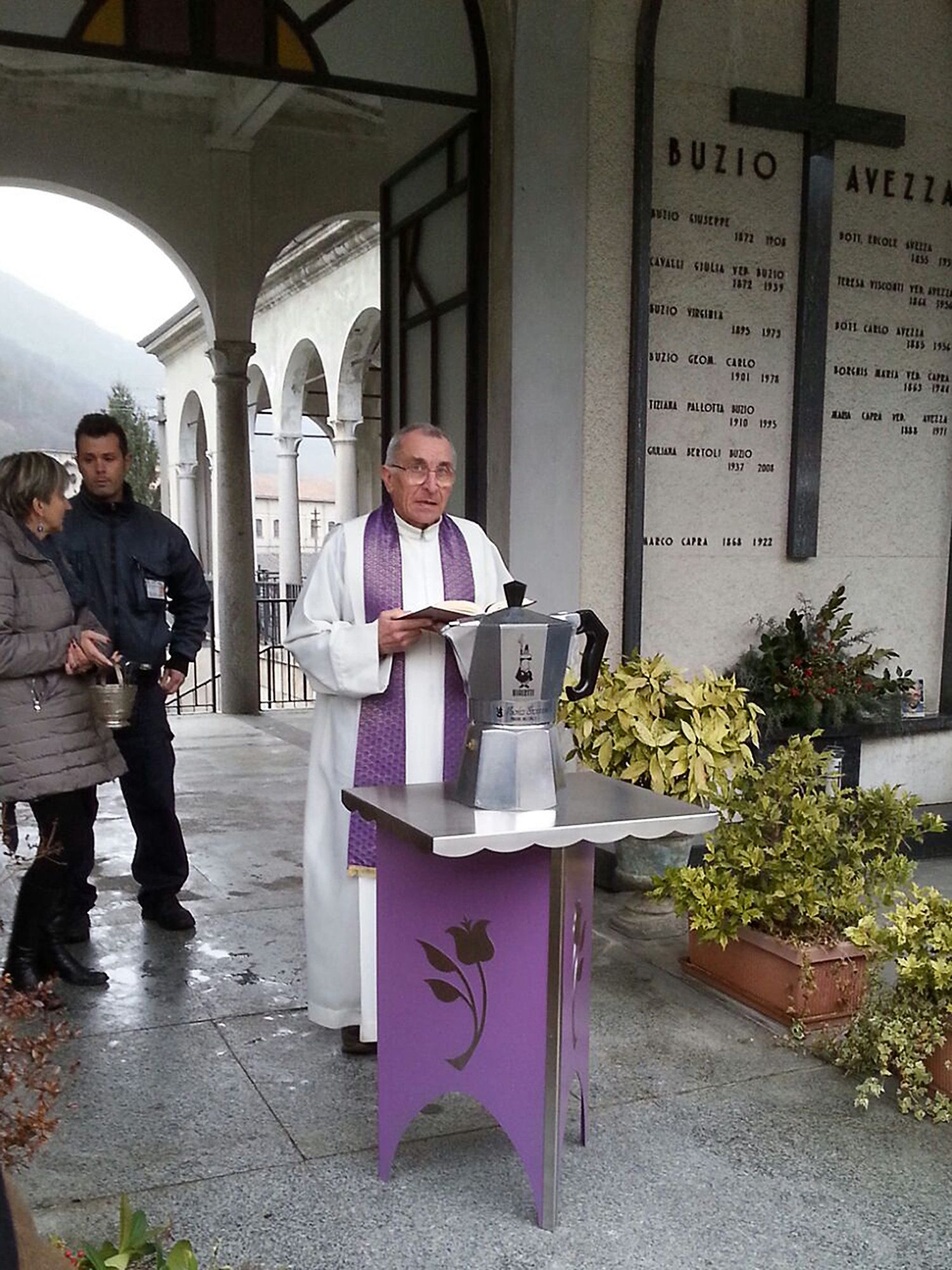 In this photo made available Wednesday, Feb. 17, 2016, father Pietro Segato, the parish priest of Casale Corte Cerro, stands in front of a Moka pot containing the ashes of Renato Bialetti, during his burial service in the cemetery of Omegna, Northern Italy, Tuesday, Feb. 16, 2016. Renato Bialetti had expressed his wish to be cremated and then buried in the Moka his father Alfonso invented in 1933. Although he was not the inventor, Renato was responsible for the extensive marketing campaign that made the Moka an icon of Italian design, exposed in museums such as the Museum Of Modern Art and many others all over the world. (AP Photo/Elisa Sola)
