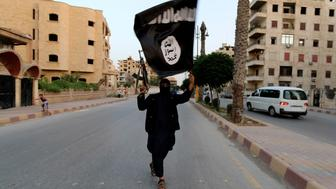 """A member loyal to the Islamic State in Iraq and the Levant (ISIL) waves an ISIL flag in Raqqa June 29, 2014. The offshoot of al Qaeda which has captured swathes of territory in Iraq and Syria has declared itself an Islamic """"Caliphate"""" and called on factions worldwide to pledge their allegiance, a statement posted on jihadist websites said on Sunday. The group, previously known as the Islamic State in Iraq and the Levant (ISIL), also known as ISIS, has renamed itself """"Islamic State"""" and proclaimed its leader Abu Bakr al-Baghadi as """"Caliph"""" - the head of the state, the statement said. REUTERS/Stringer (SYRIA - Tags: POLITICS CIVIL UNREST TPX IMAGES OF THE DAY)  FOR BEST QUALITY IMAGE ALSO SEE: GF2EAAO0VU501"""