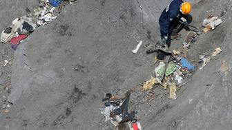 A French rescue worker inspects the debris from the Germanwings Airbus A320 at the site of the crash, near Seyne-les-Alpes, French Alps March 29, 2015. The young German co-pilot, Andreas Lubitz, suspected of deliberately crashing a passenger plane in the French Alps, killing all 150 people on board including himself, told his girlfriend he was in psychiatric treatment, and that he was planning a spectacular gesture that everyone would remember, the German daily Bild reported on Saturday. Picture taken March 29, 2015.    REUTERS/Gonzalo Fuentes
