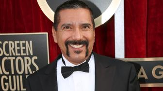 """FILe - In this Jan. 18, 2014 file photo, Steven Michael Quezada an actor on the series """"Breaking Bad,"""" arrives at the 20th annual Screen Actors Guild Awards in Los Angeles. Quezada is jumping in a race for a heated county commissioner seat in Albuquerque. Quezada, who played DEA agent Steven Gomez in the hit AMC-TV series """"Breaking Bad"""", said Monday, July 20, he will announce this week that he will run for the Bernalillo County Commission. (Photo by Matt Sayles/Invision/AP, File)"""