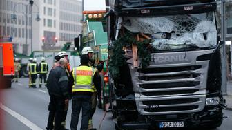 Fire fighters stand beside the truck which ploughed last night into a crowded Christmas market in the German capital Berlin, Germany, December 20, 2016.      REUTERS/Hannibal Hanschke