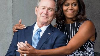 Former US President George W. Bush receives a hug from US First Lady Michelle Obama as they attend the opening ceremony for the Smithsonian National Museum of African American History and Culture on September 24, 2016 in Washington, D.C.  / AFP / ZACH GIBSON        (Photo credit should read ZACH GIBSON/AFP/Getty Images)