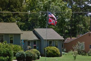 In a photo taken last year, aConfederate flag is seen flying outside the home of the former Roswell, Georgia, police se