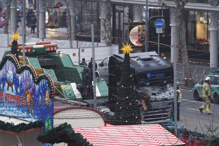 Security and rescue workers tend to the area after a lorry truck ploughed through a Christmas market on December 20, 2016 in