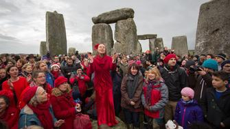 AMESBURY, ENGLAND - DECEMBER 22:  Susie Ro Prater (C) leads the Shakti Sings choir as druids, pagans and revellers gather in the centre of Stonehenge, hoping to see the sun rise, as they take part in a winter solstice ceremony at the ancient neolithic monument of Stonehenge near Amesbury on December 22, 2015 in Wiltshire, England. Despite a forecast for rain, a large crowd gathered at the famous historic stone circle - a UNESCO listed ancient monument - to celebrate the sunrise closest to the Winter Solstice, the shortest day of the year - an event is claimed to be more important in the pagan calendar than the summer solstice, because it marks the 're-birth' of the Sun for the New Year.  (Photo by Matt Cardy/Getty Images)