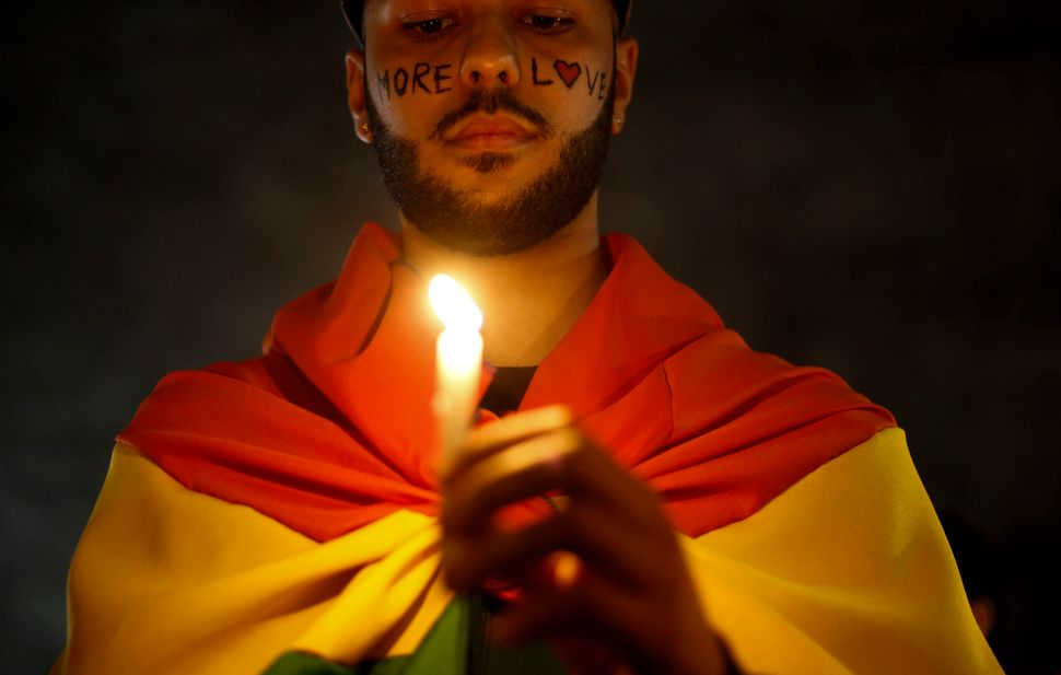 Activists carrying lit candles and flags participate in a vigil in São Paulo, Brazil, to pay tribute on June 15 to the