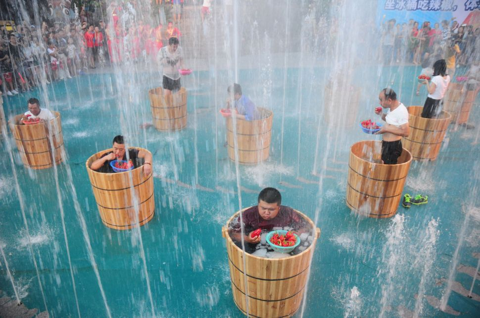 Tourists sitting in ice buckets eat peppers in a fountain during a competition at Song Dynasty Town on July 20 in Hangzhou, Z