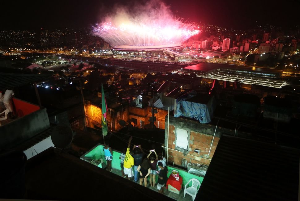 Fireworks explode over Maracanã stadium with the Mangueira favela community in the foreground during opening cer