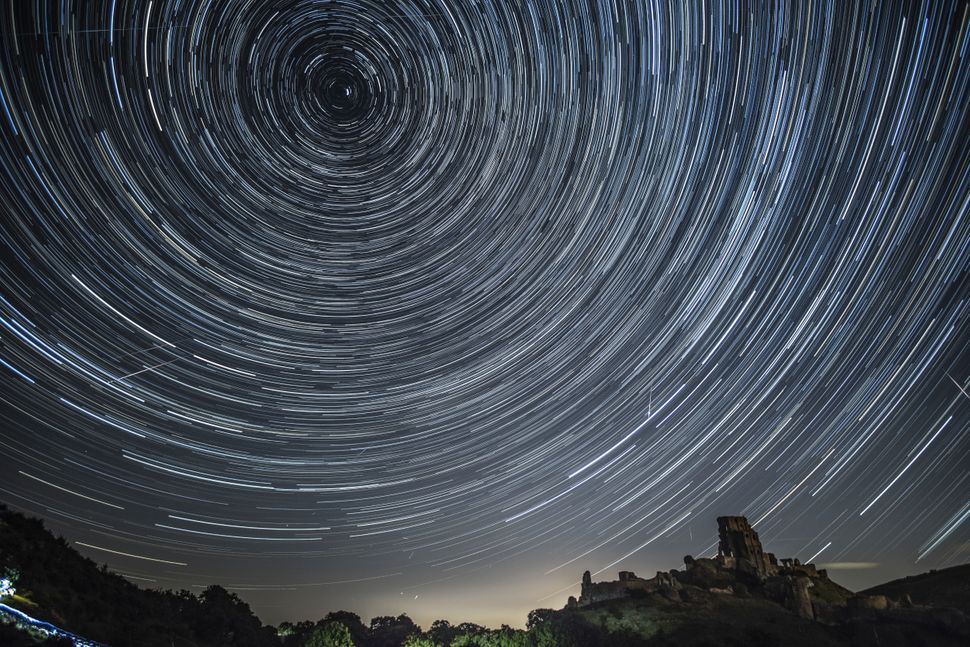 Satellites, planes and comets transit across the night sky under stars that appear to rotate above Corfe Castle on Aug. 12 in
