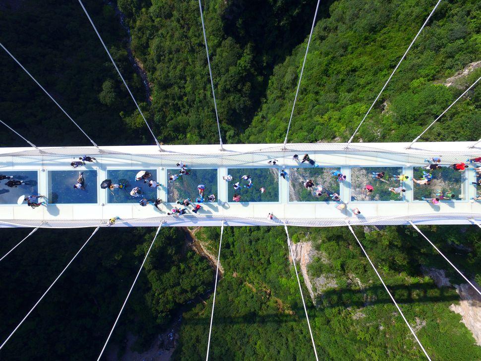 An aerial photo shows tourists visiting the glass-bottom bridge at Zhangjiajie Grand Canyon on Aug. 20 in Zhangjiajie, Hunan